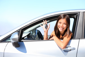 Asian car driver woman smiling showing new car keys and car. Mixed-race Asian and Caucasian girl.